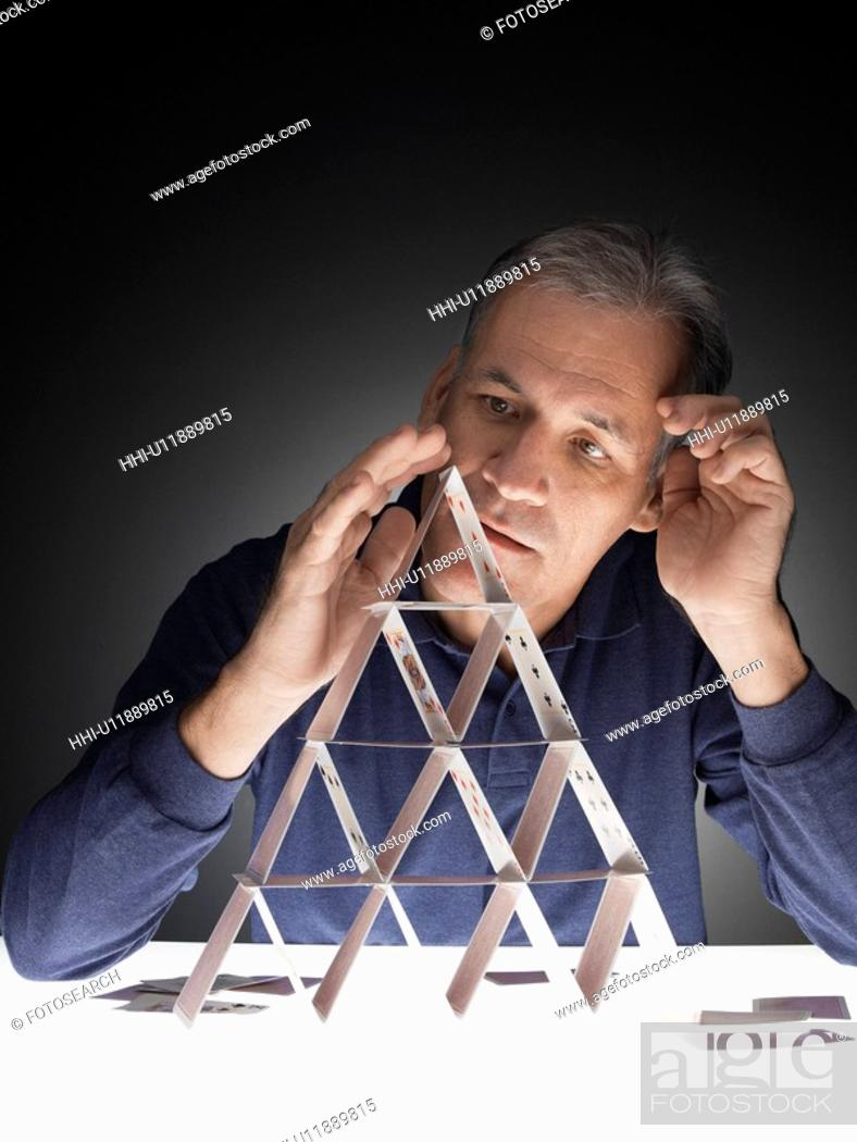 Stock Photo: Mature man building house of cards.
