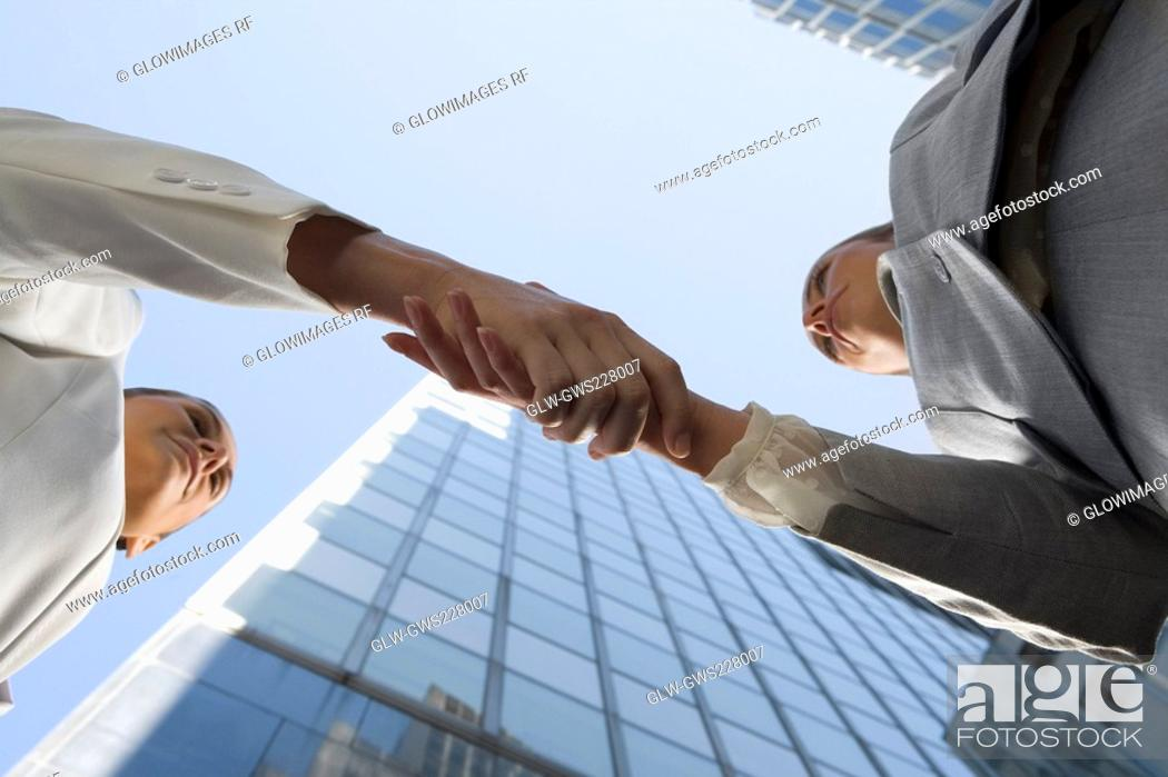 Stock Photo: Low angle view of two businesswomen shaking hands.