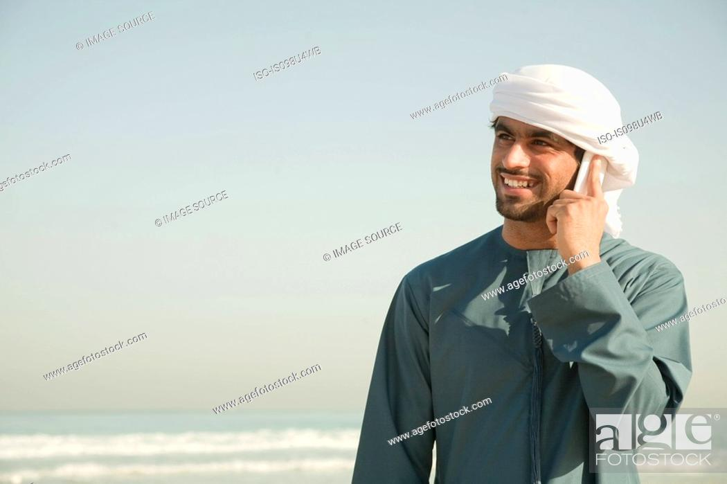 Stock Photo: Middle Eastern man using mobile phone on the beach.