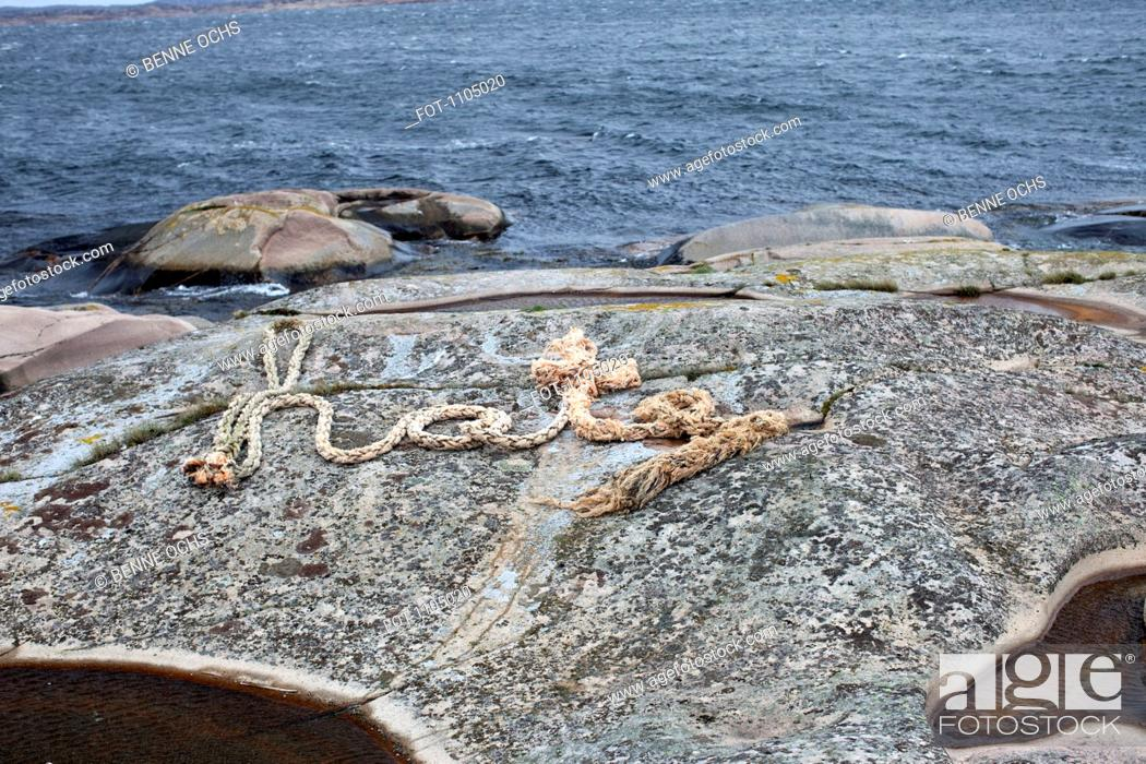 Stock Photo: A rope spelling HATE on a rocky coastline.