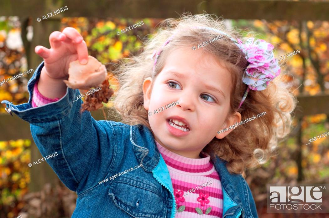 Stock Photo: Young girl, three years old, outside during Autumn marvelling at nature and fungi mushroom she has found.