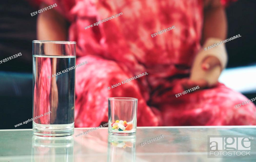 Stock Photo: Senior asian woman take pill medicine on hand while sitting on sofa at home.