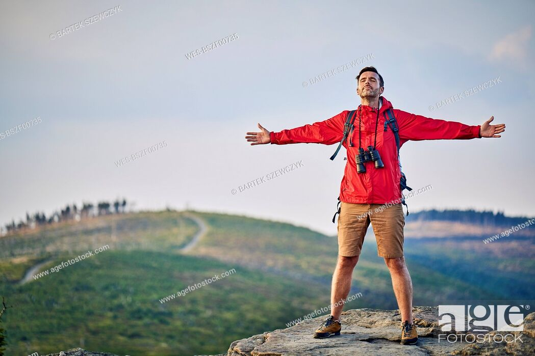 Stock Photo: Man standing with outstretched arms on mountain top.