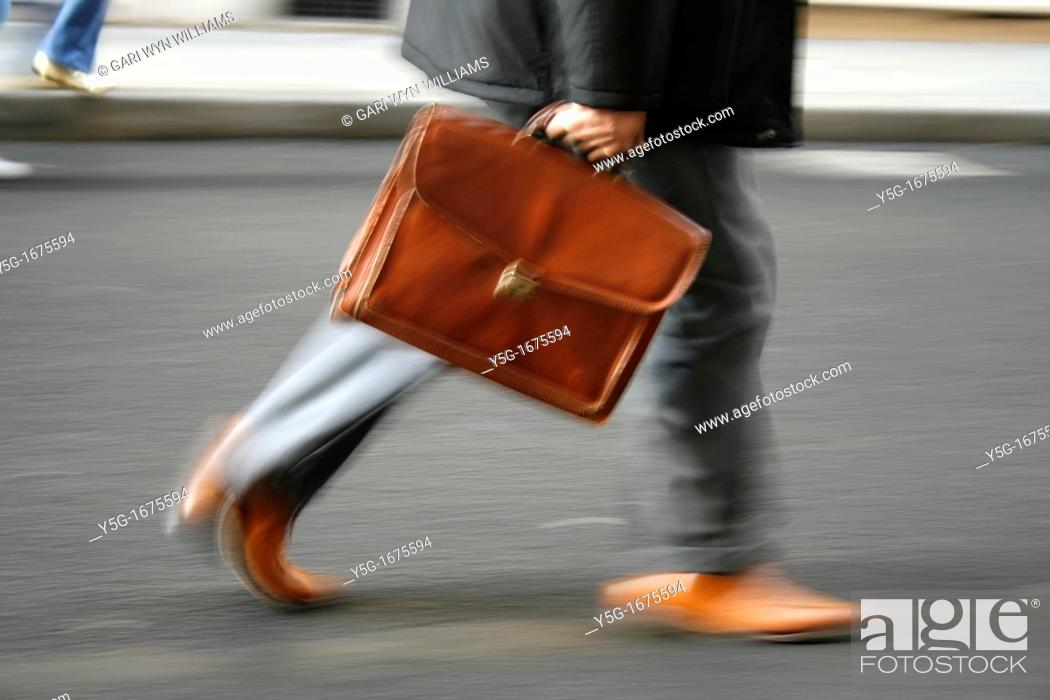Stock Photo: one male commuter carrying briefcase in town.