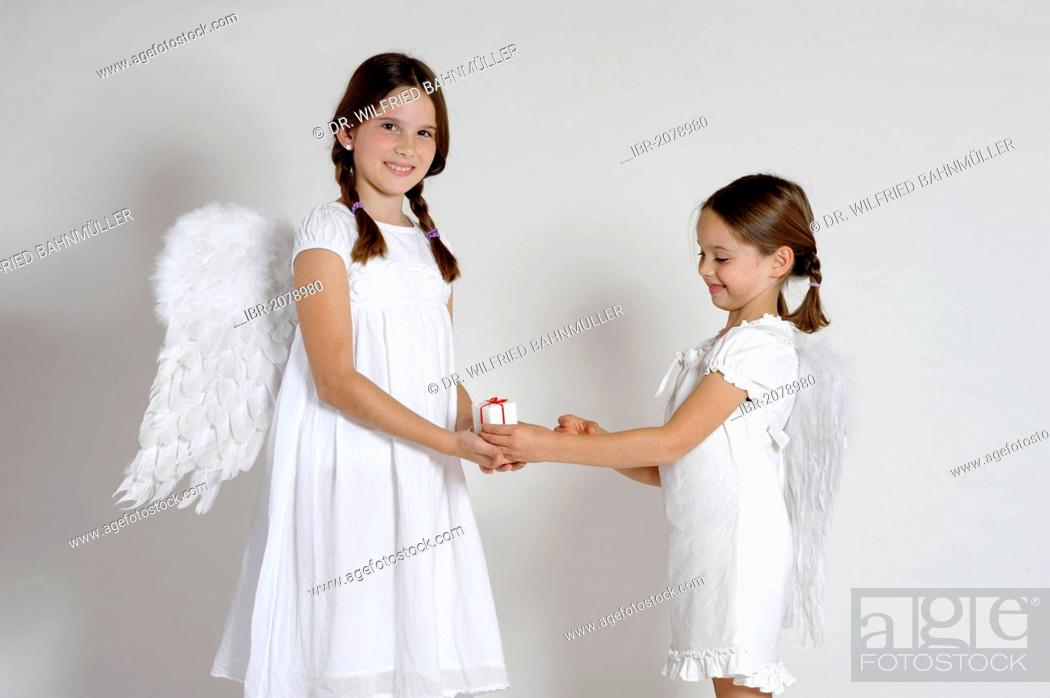 Stock Photo: Two girls dressed up as Christmas angels, with a gift, Christmas.