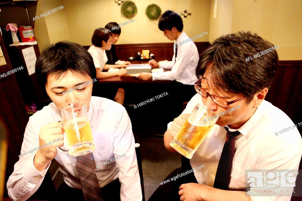 Stock Photo: Japanese businessman drinking with his boss at a Japanese style Izakaya.