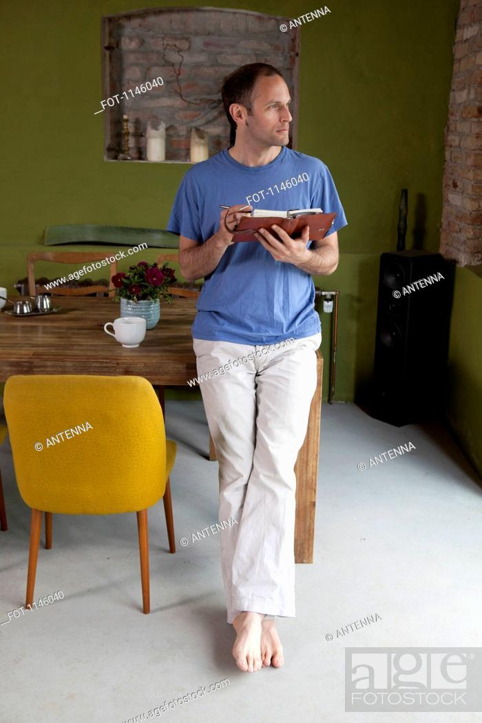 Stock Photo: A man leaning on a dining table holding a journal and a pen, looking away.