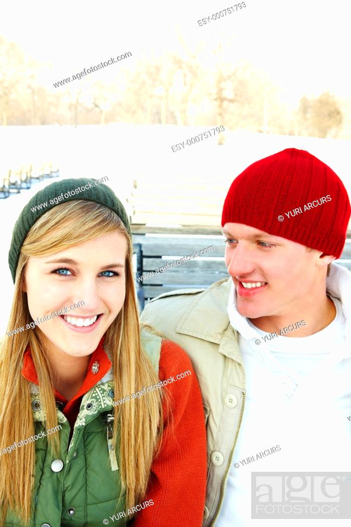 Stock Photo: Closeup portrait of a young couple sitting outside on a bench.