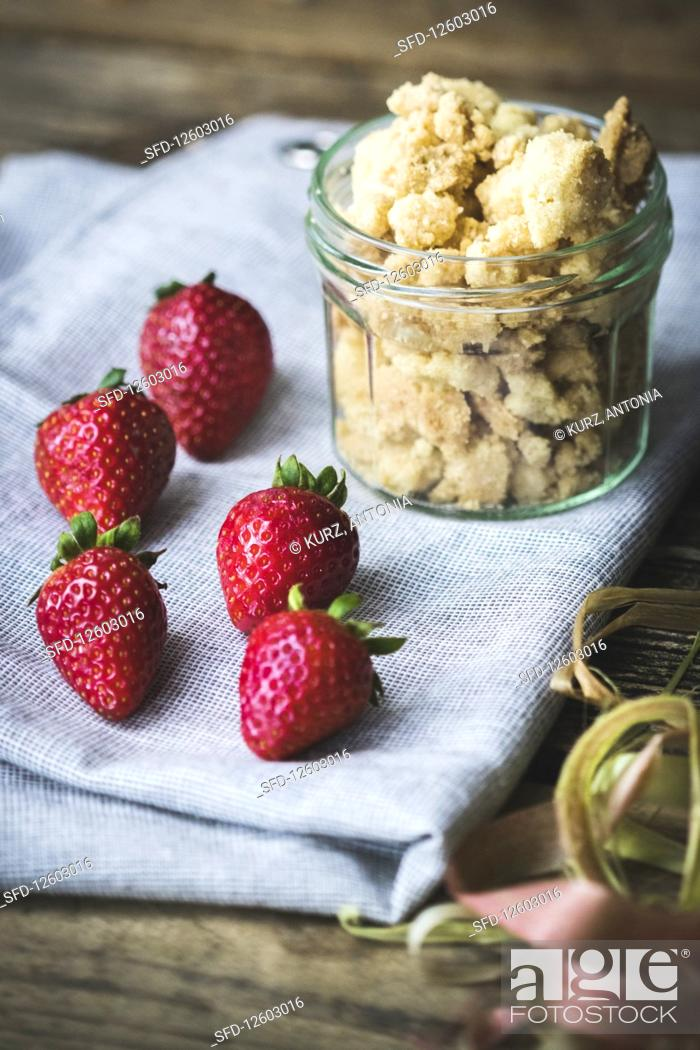 Photo de stock: Strawberries and a jar of crumbles as ingredients for cake or dessert.