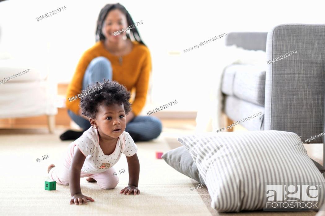 Stock Photo: Black woman watching baby daughter crawl toward pillow.