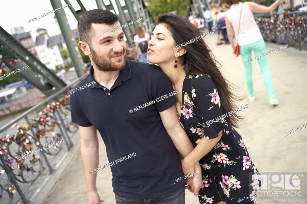 Stock Photo: Young couple walking on bridge. Eisener Steg, Frankfurt am Main, Germany.