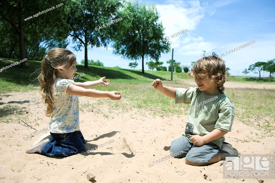 Stock Photo: Young children playing in sand at park.