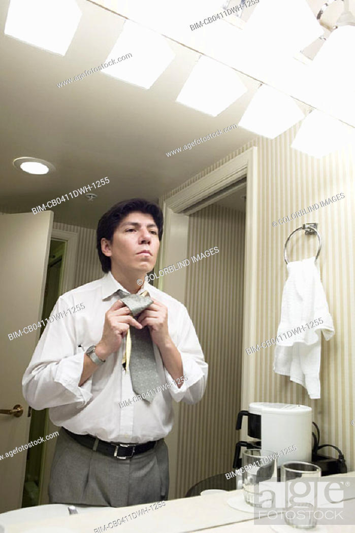 Stock Photo: Businessman getting dressed in bathroom.