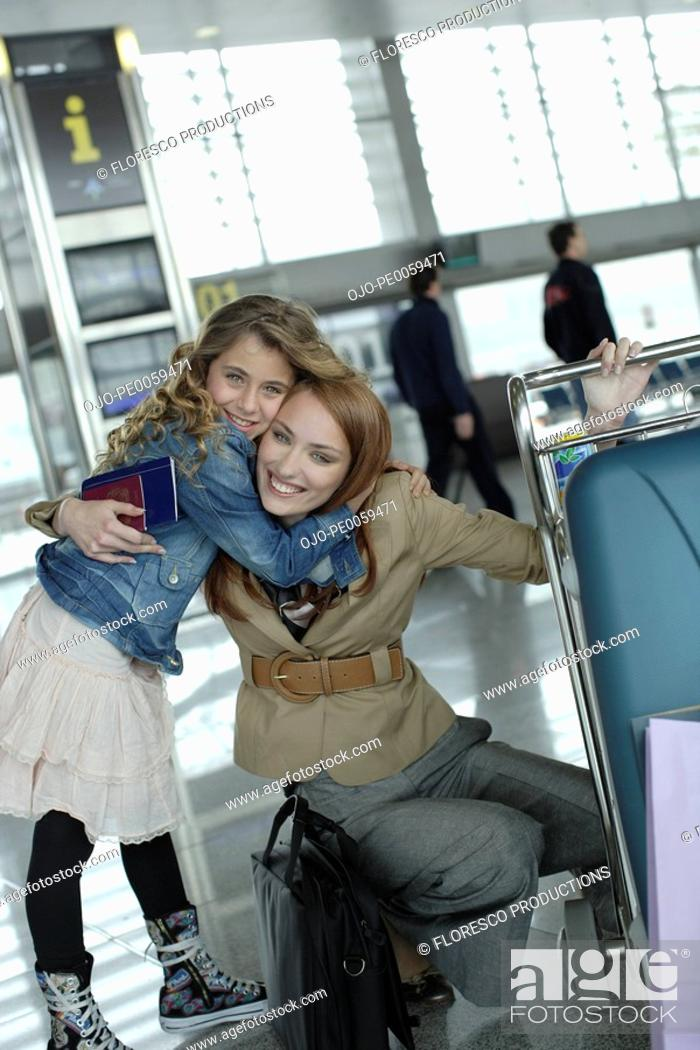Stock Photo: Woman and young girl in airport hugging.