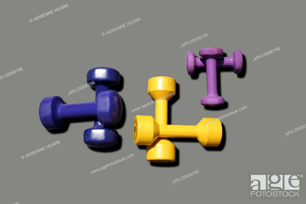 Stock Photo: Three sets of crossed free weights on plain background.