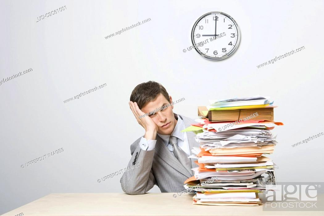 Stock Photo: Businessman next to stack of paperwork.