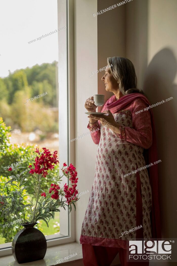 Stock Photo: Older woman standing at window with cup of tea.