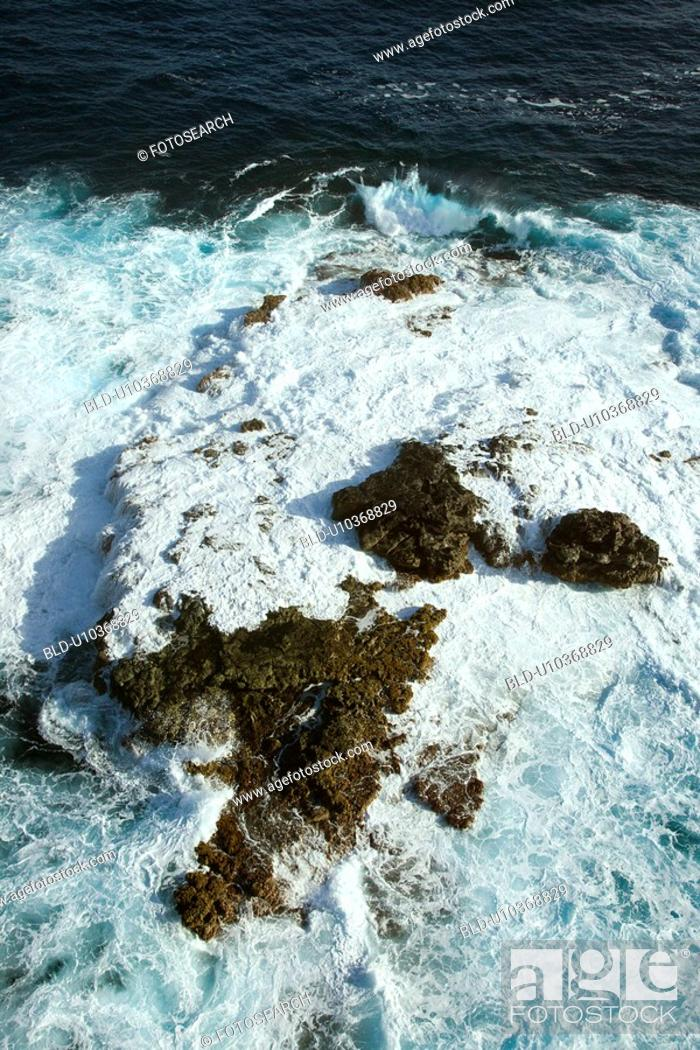 Stock Photo: Aerial view of rocks in Pacific ocean with water swirling around them off the coast of Maui, Hawaii.