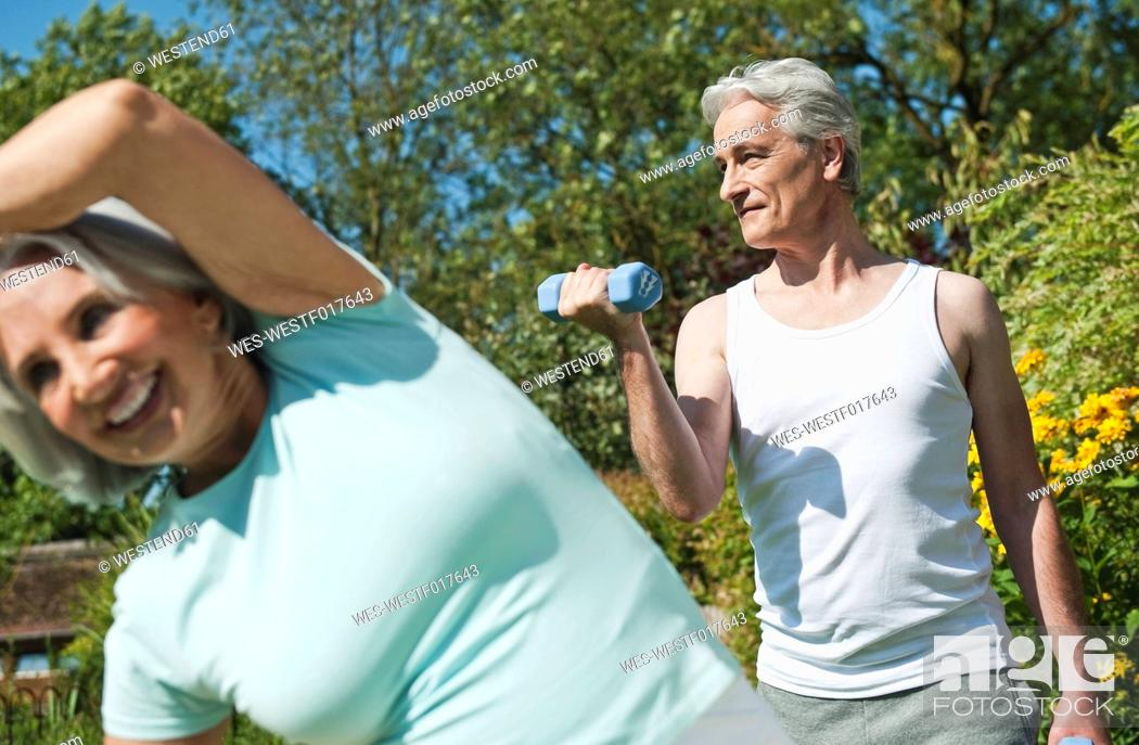 Stock Photo: Germany, Bavaria, Man lifting dumbells and woman exercising in garden, smiling.