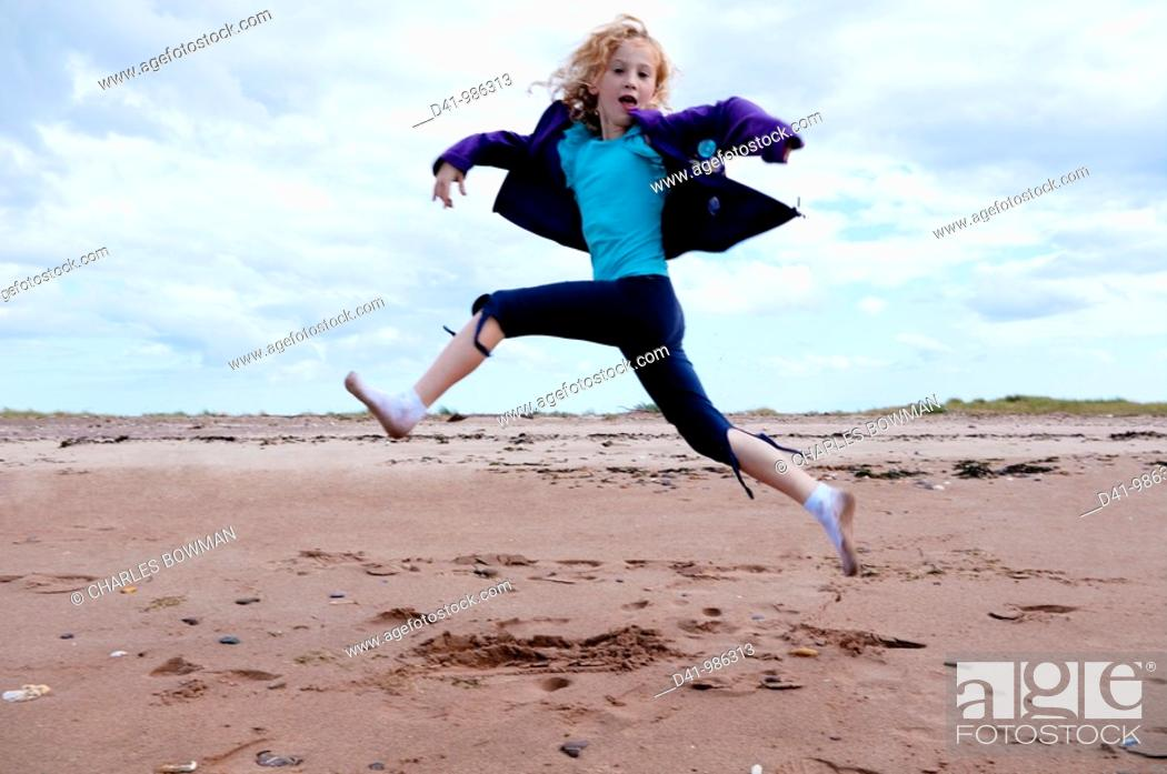 Stock Photo: child girl leaping over beach.