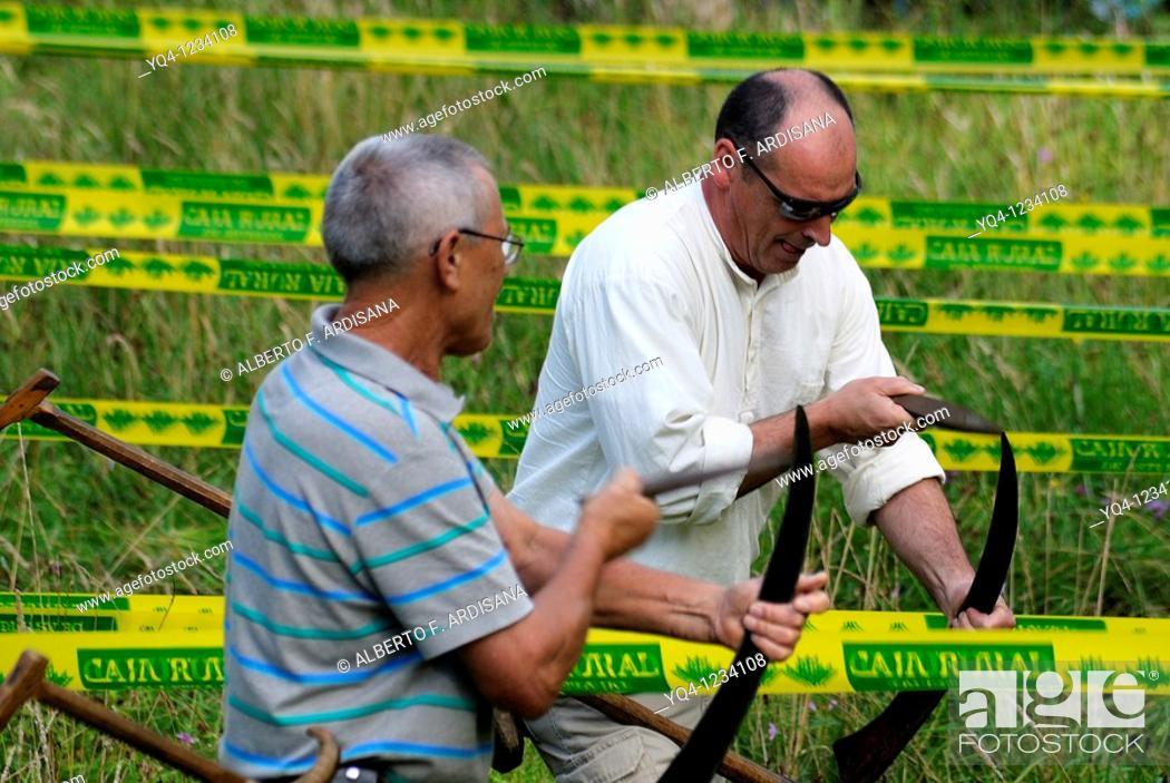 Stock Photo: Asturian traditional sports, championship hay mowers sharpening their scythes Two Benia de Onis, Asturias, Spain.