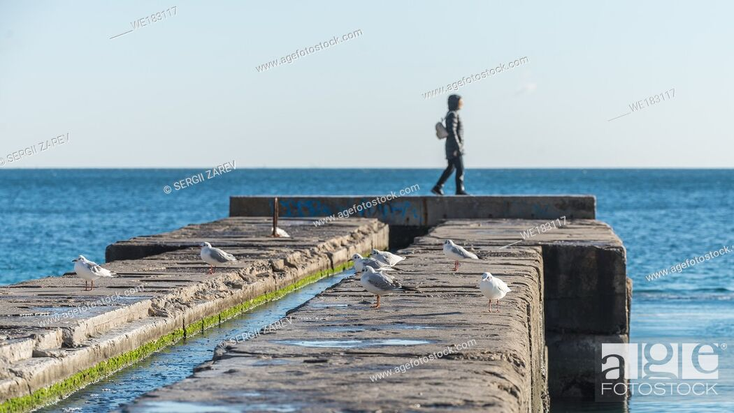 Stock Photo: Odessa, Ukraine - 12. 27. 2018. Lonely people on the pier by the sea on a sunny winter day.