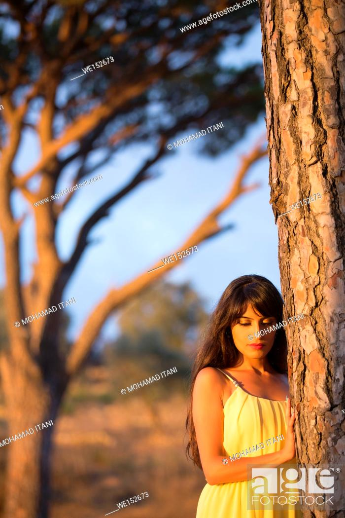 Stock Photo: Sad woman leaning against a tree.