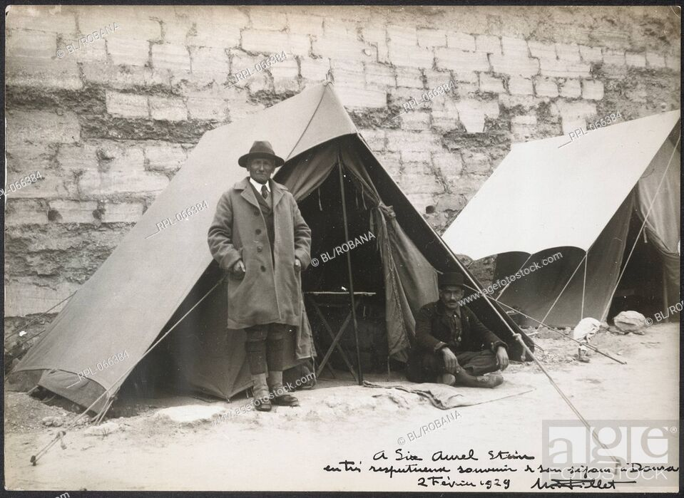 Imagen: Full-length portrait of Sir Aurel Stein, standing in front of his tent pitched in front of a wall. Originally published/produced in February 1929 Illustrated by.