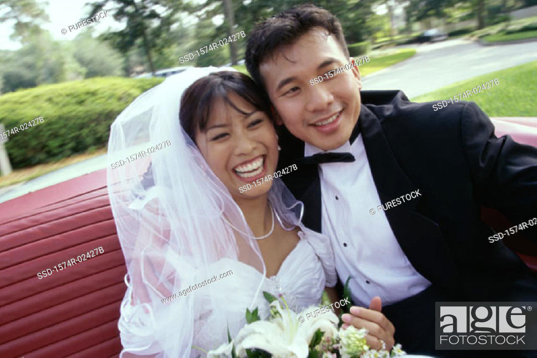 Stock Photo: Newlywed couple sitting in a convertible car.