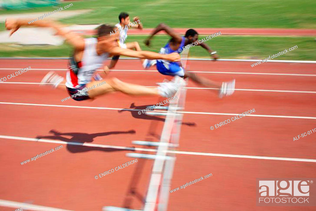Stock Photo: Male Runners Clearing Hurdle.
