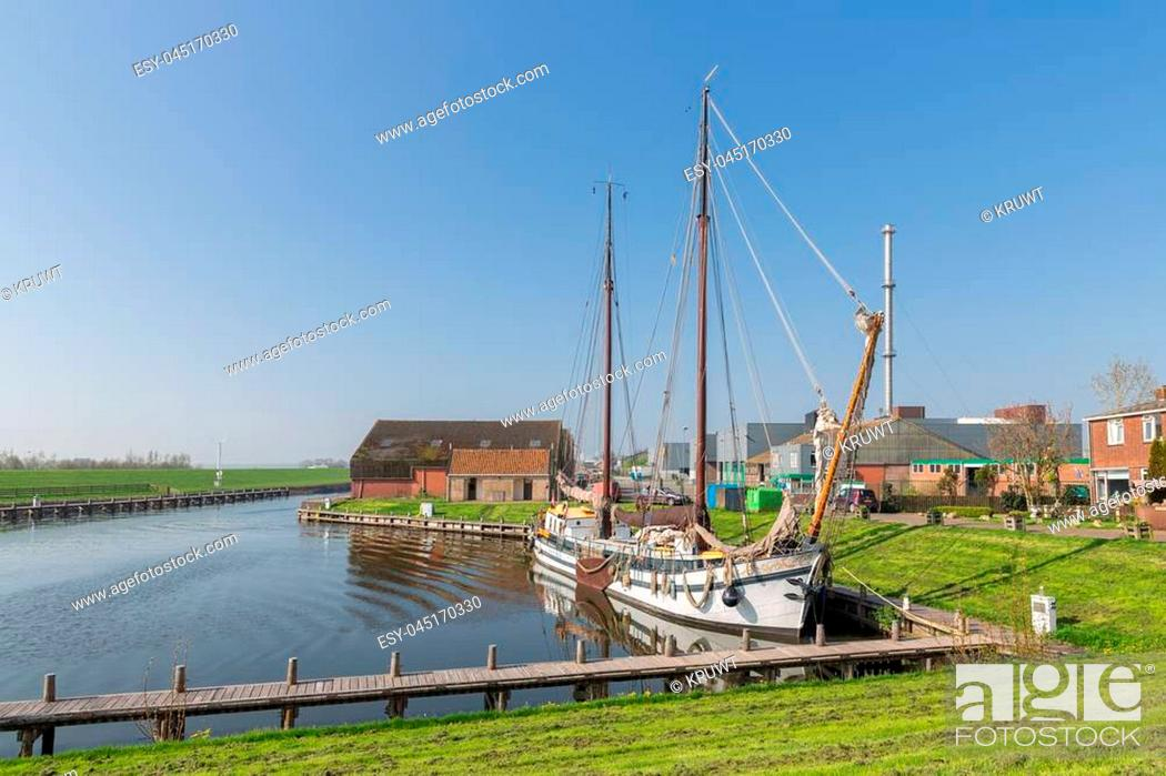 Photo de stock: Outer harbor with wooden sailing vessel in old historic Dutch fishing village Workum.