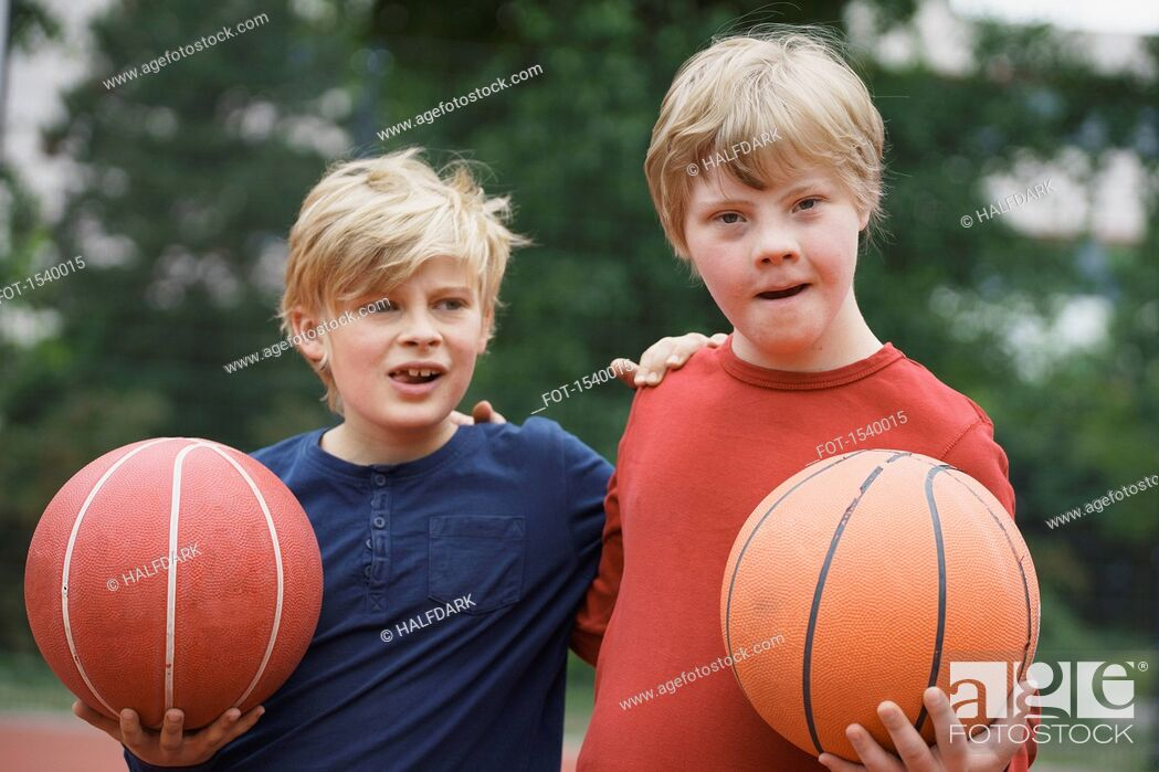 Stock Photo: Brothers standing arms around while holding basketballs in park.