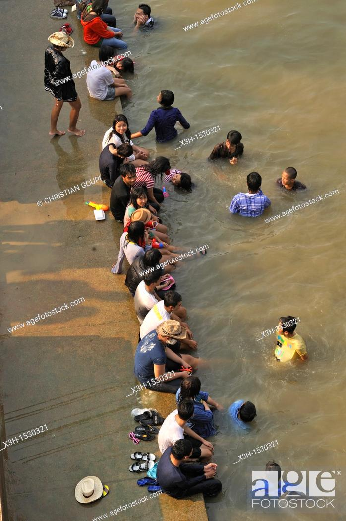 Stock Photo: young people bathing into the Chao Praya river, Songkran festival, New Year's Day, Ayutthaya, Thailand, Asia.