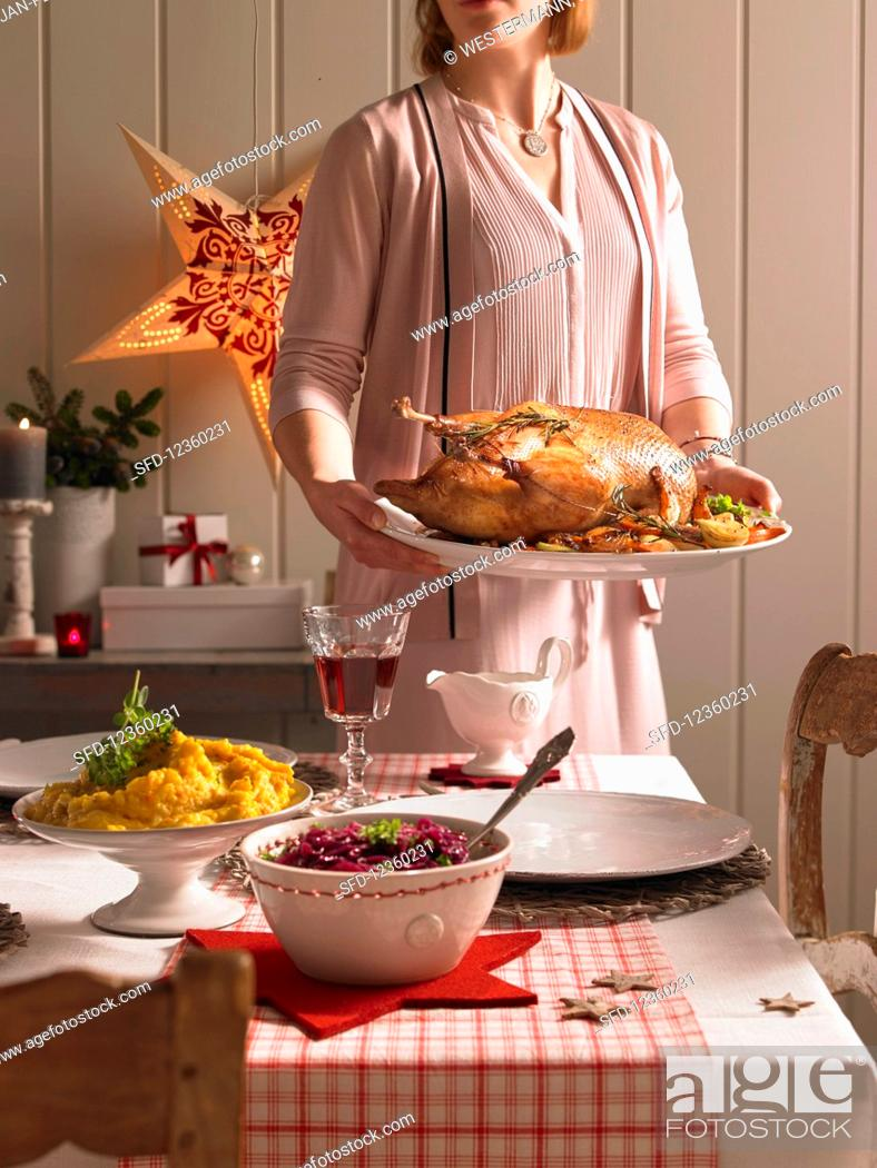 Stock Photo: A woman serving a roast goose (Christmas).