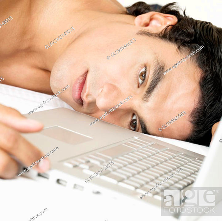 Stock Photo: Close-up of a young man lying near a laptop.