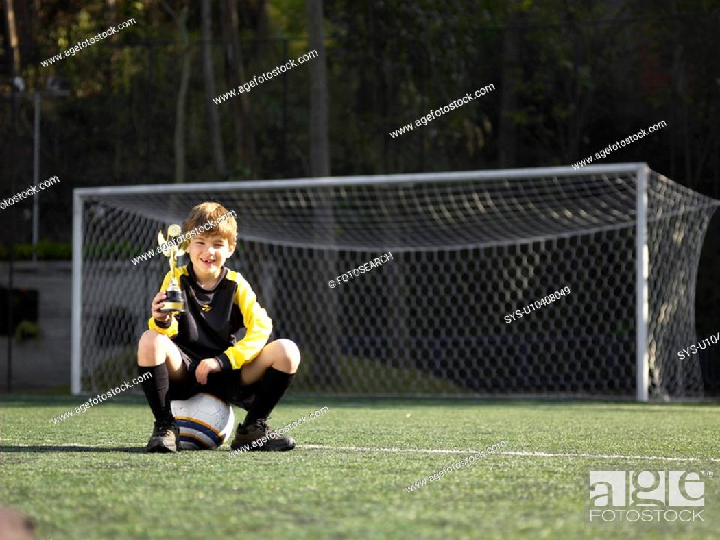 Stock Photo: Boy sitting on soccer ball and holding trophy portrait.