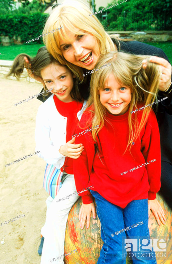 Stock Photo: Portrait of mature adult with two young girls.