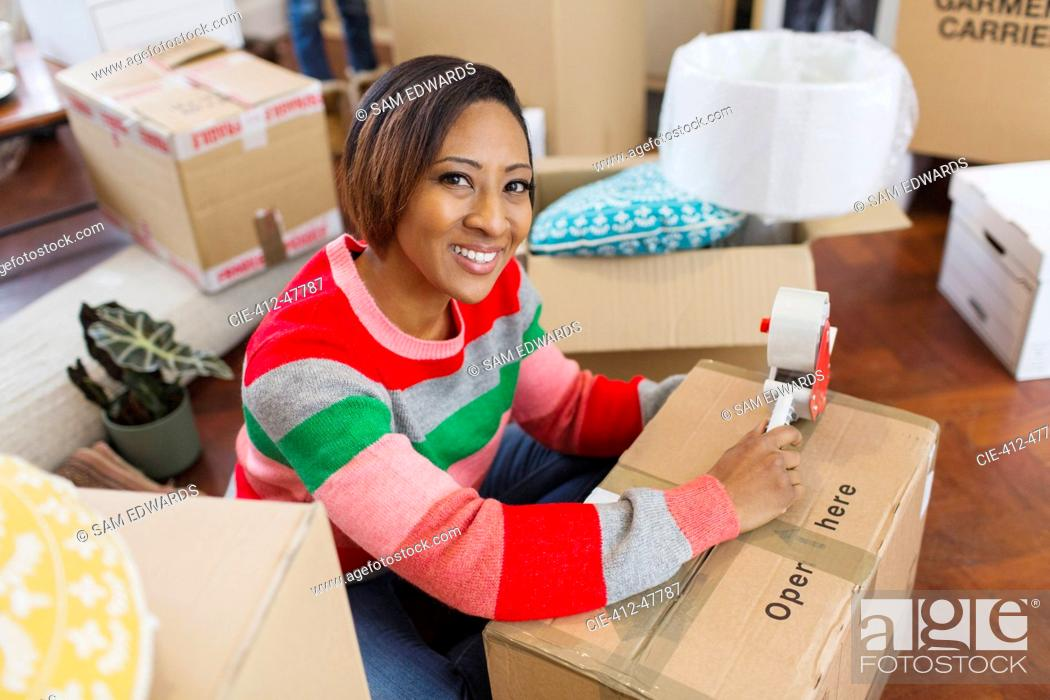 Stock Photo: Portrait smiling, confident woman packing moving boxes.