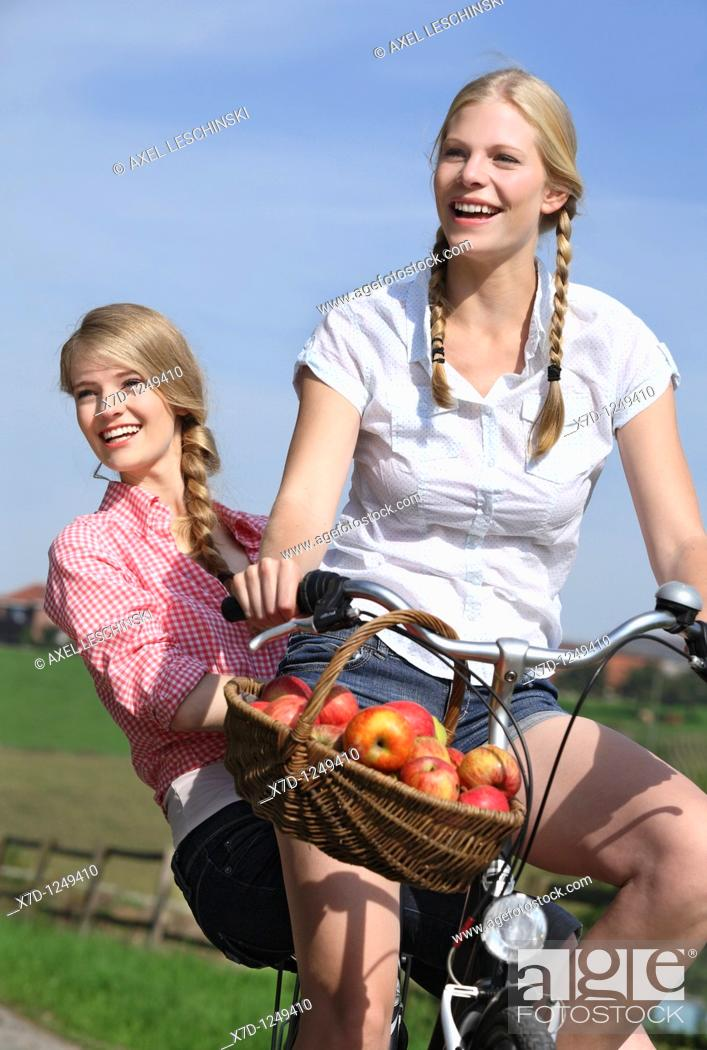 Stock Photo: two young woman on one bike.