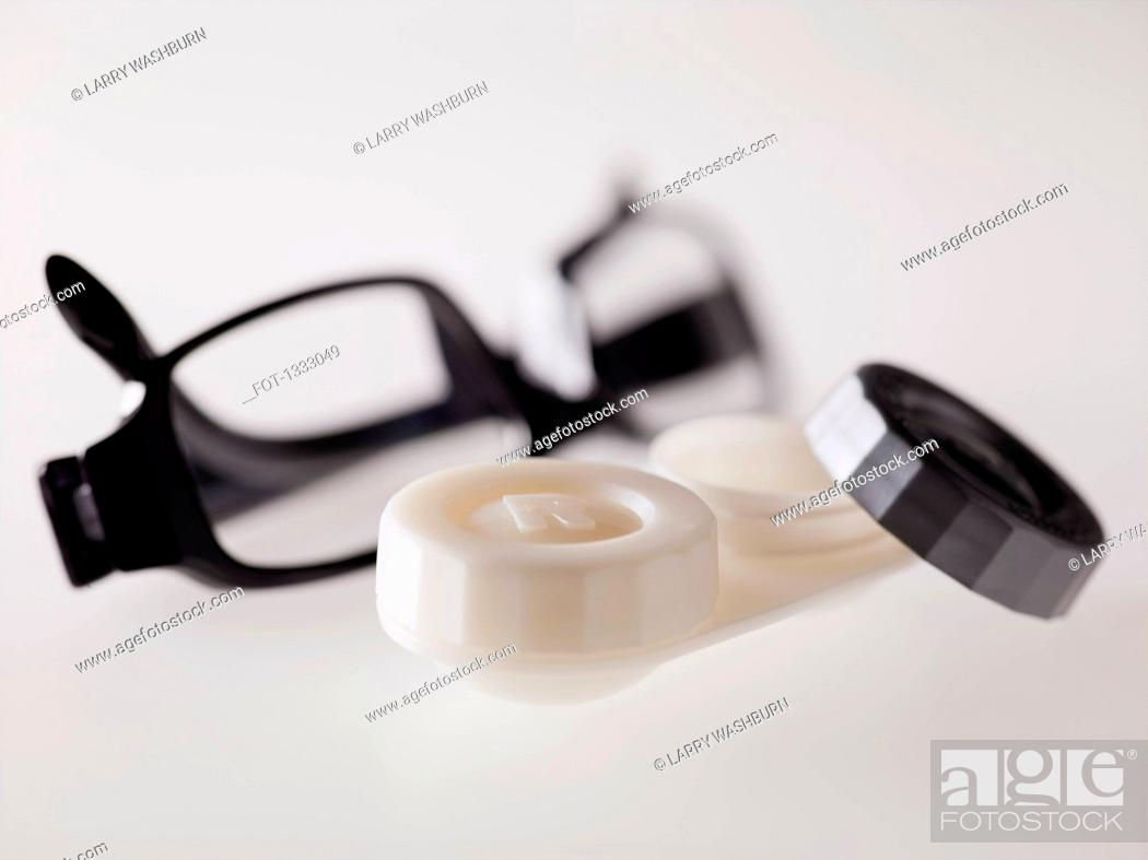 Stock Photo: Contact lens case and glasses over gray background.