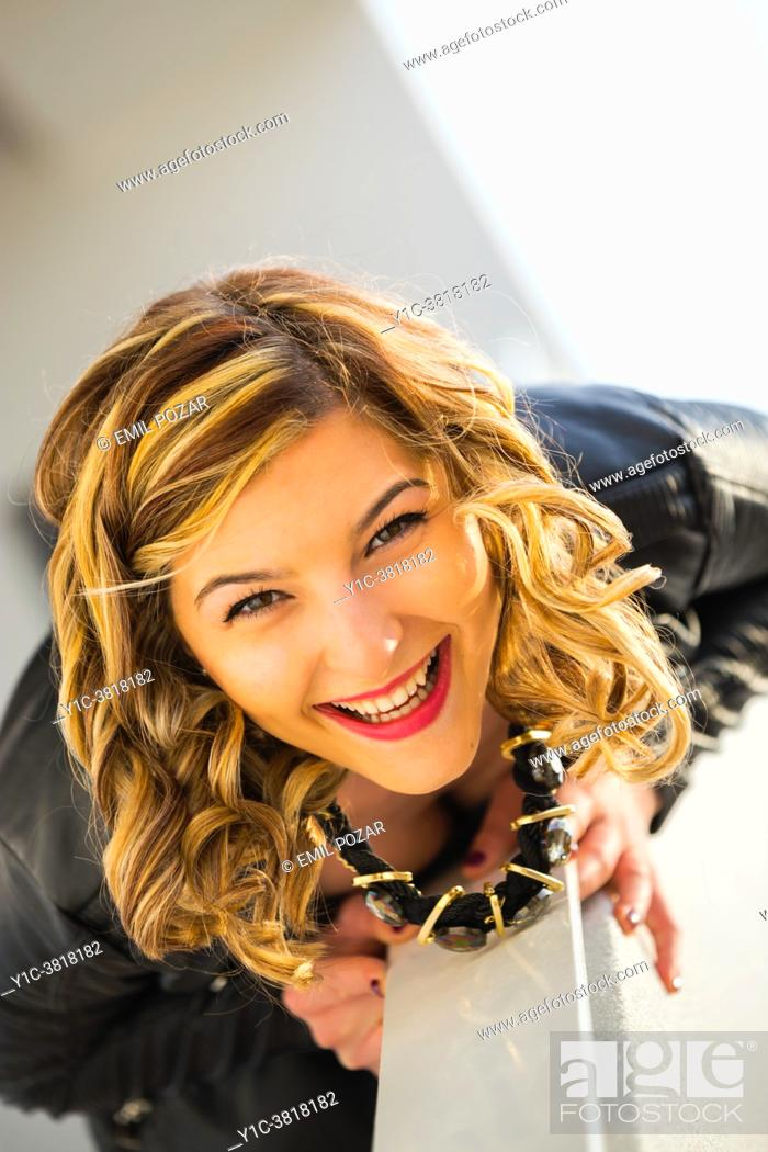 Stock Photo: Blonde curly hair teen girl laughing at camera.