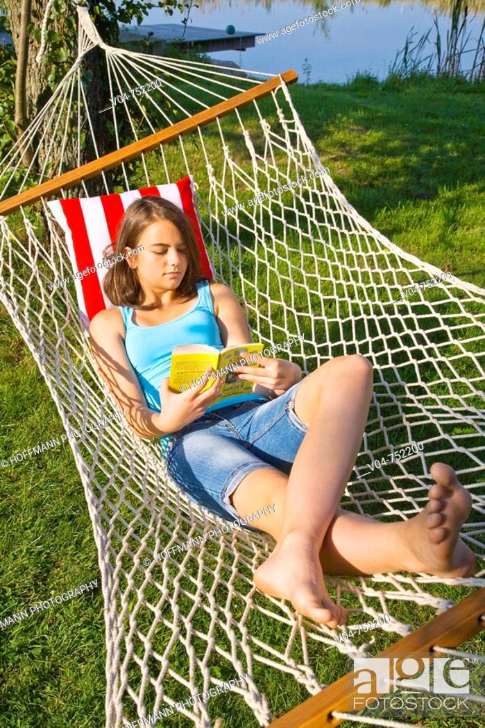 Stock Photo: Teenaged girl reading a book in a hammock outdoors in a garden.