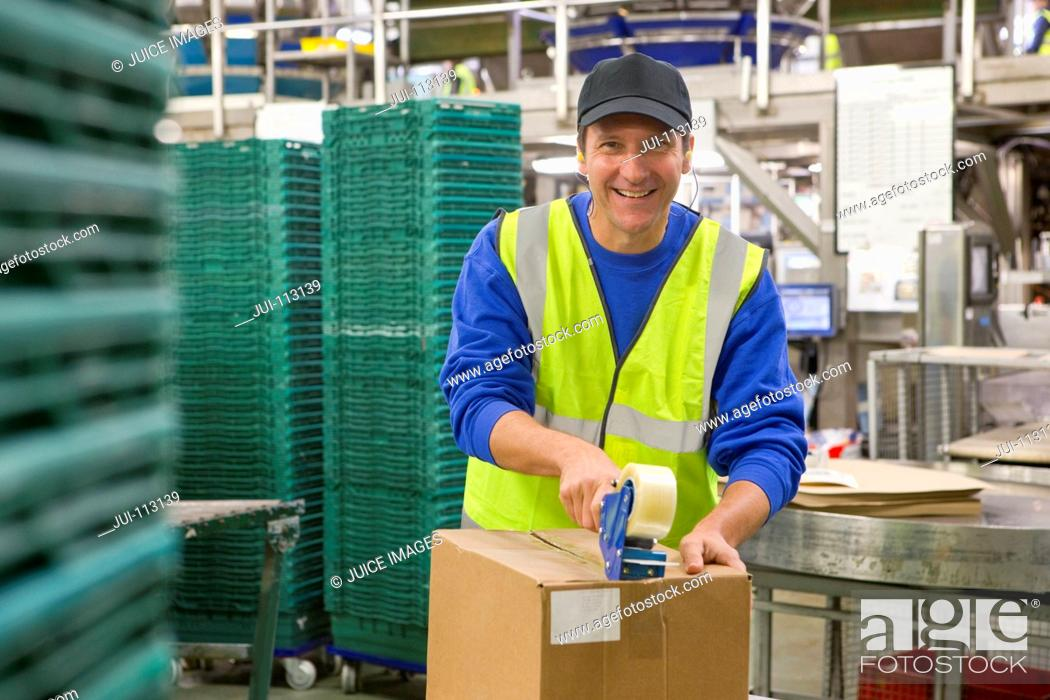 Imagen: Portrait confident worker taping box in food processing plant.