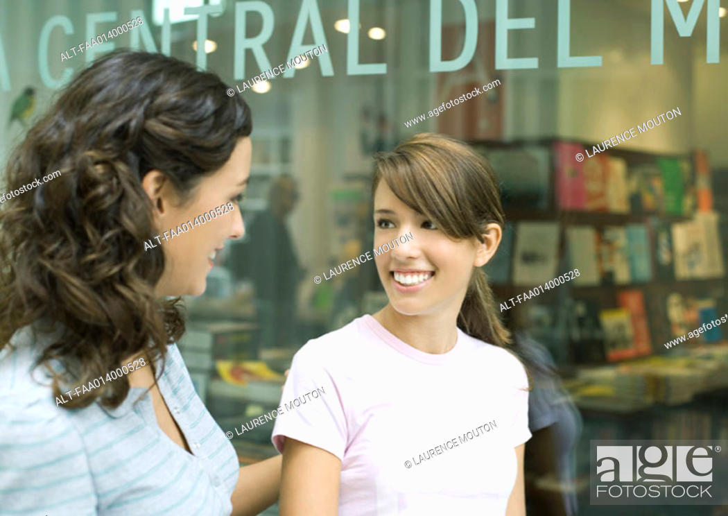Stock Photo: Two teenage girls standing in front of a bookshop.
