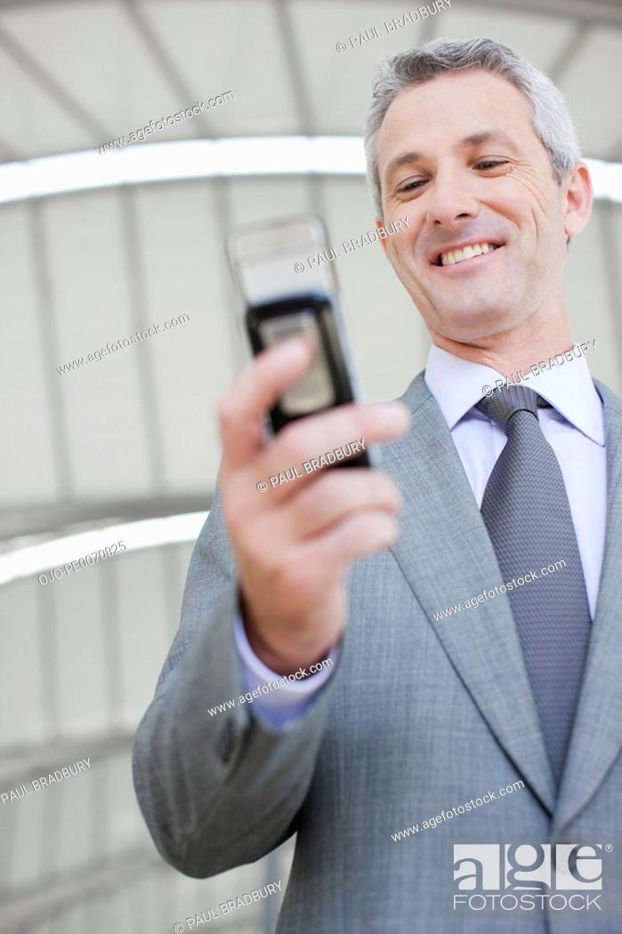 Stock Photo: Businessman text messaging on cell phone.