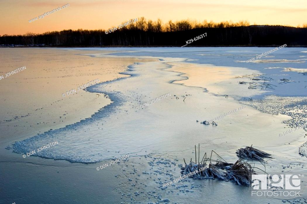 Stock Photo: Dawn skies reflected in fresh ice of frozen bay in Kelly Lake.