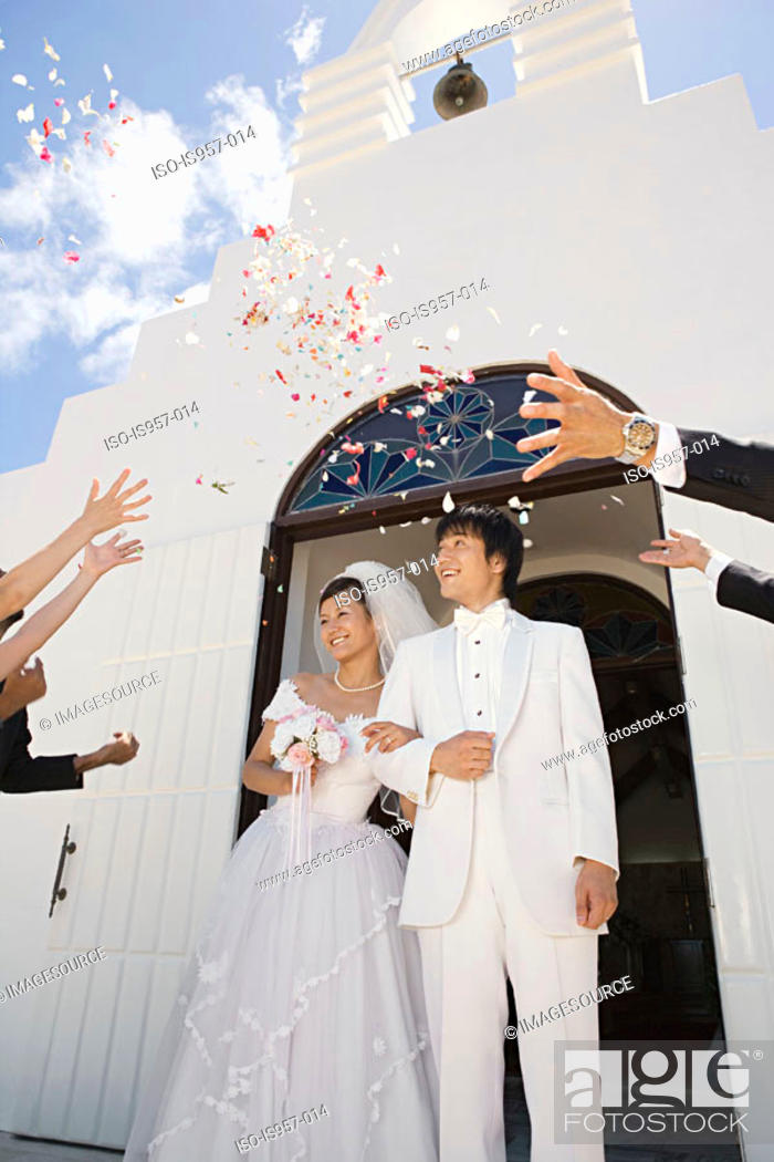 Stock Photo: Guests throwing confetti over newlyweds.