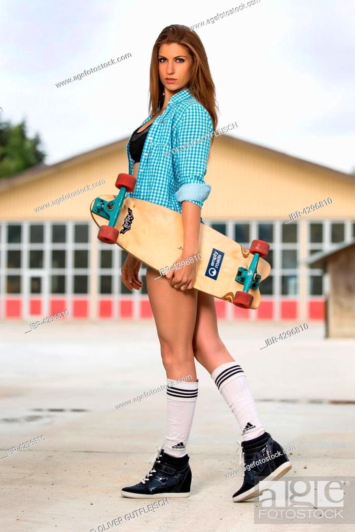 Stock Photo: Young woman posing with skateboard.