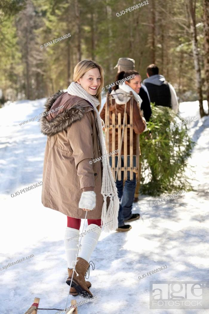 Stock Photo: Portrait of friends with sleds and fresh cut Christmas tree in woods.