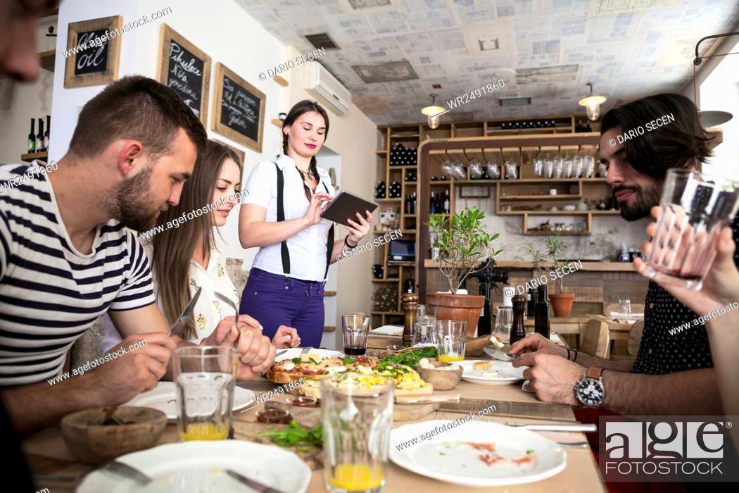 Stock Photo: Waitress serving friends in restaurant.
